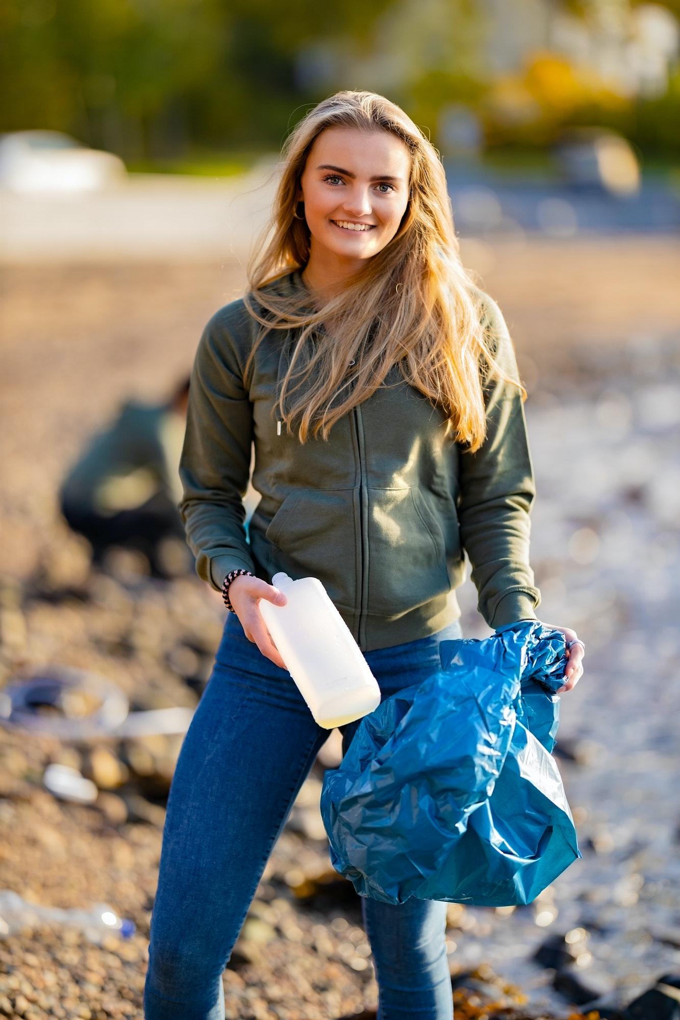 smiling-female-volunteer-holding-bottle-and-garbage-bag-at-beach.jpg